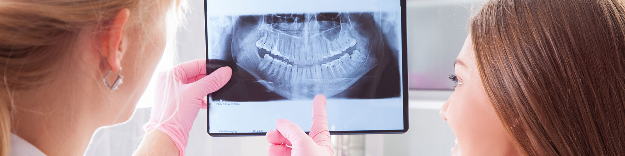 dentist looking at x-ray with patient
